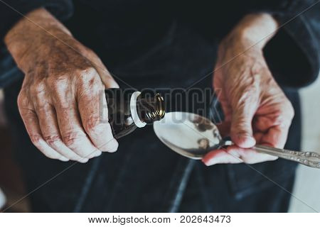 Elderly woman pours medicine in spoon to take medication, health care of elderly people concept, selective focus, toned