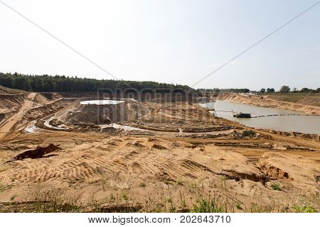 Extraction in a sand quarry with powerful machines and a washing lake.