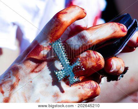 Christian religion symbol cross hands young woman bleeding zombiewalk fake blood