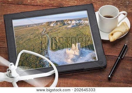 Castle Rock  - limestone pillar landmark in prairie of western Kansas near Quinter, reviewing aerial image on a digital tablet
