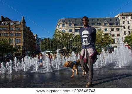 Man And Dog By The Picadilly Gardens Water Fountains, Manchester