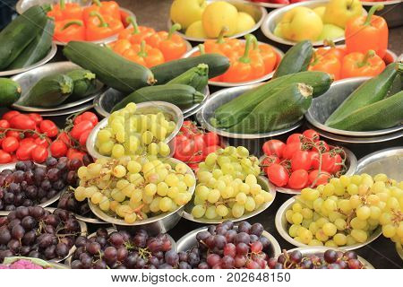 Fresh fruits and vegetables on a market stall: grapes tomatoes courgette and peppers displayed in small metal bowls