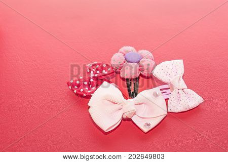 Three buckles with a bow and another with a flower shape for the hair. On red background.
