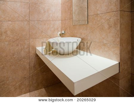 Decorated and tiled bathroom with white porcelain sink in a new bathroom