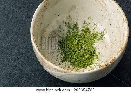 Matcha green tea powder in ceramic matcha chawan bowl. Matcha is made of finely ground green tea powder. It's very common in japanese culture. Matcha is healthy due to it's high antioxydant count.