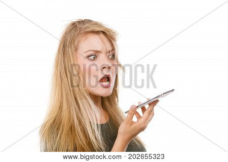 Unpleasant conversation bad relationships concept. Screaming furiously angry young blonde woman talking on phone. Studio shot isolated