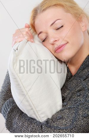 Sleep time warm bedding tiredness concept. Happy sleepy tired woman smiling and holding cozy white pillow