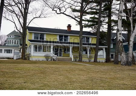 WEQUENTONSING, MICHIGAN / UNITED STATES - MARCH 30, 2017: A large yellow home on Beach Drive in Wequetonsing.