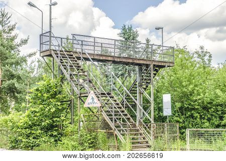 Old stairways over railway overgrown with green bushes