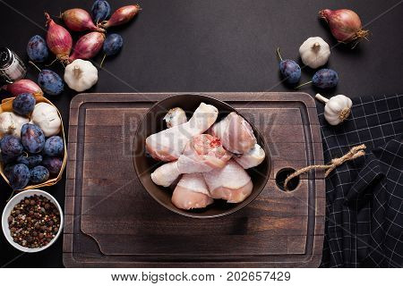 Closeup of a bowl of raw chicken thighs with the garlic, salt and a mixture of peppers on dark background. Top view. Around the cutting boards are also shallots and prunes.