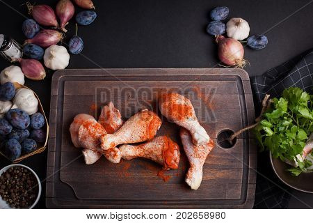 Closeup of raw chicken thighs with garlic, paprika, salt and pepper mixture on a dark background. Top view. Around the cutting Board also shallots and plums.