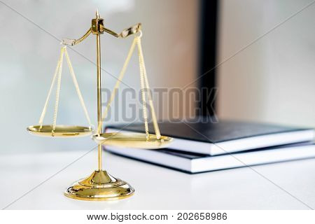 Law scales or golden weight and legals books on table. Symbol of justice.