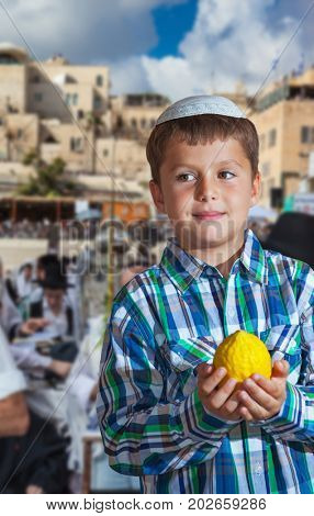 Autumn Jewish holiday Sukkot. Jerusalem, Israel. Beautiful Jewish boy with green eyes, in a white skullcap, with citrus in his hand