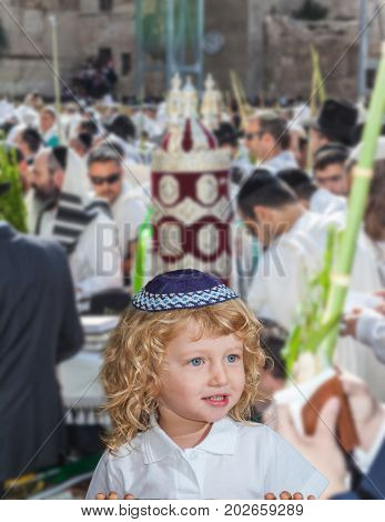 Handsome little boy with blue eyes and blond side curls, in skullcap. Autumn Jewish holiday Sukkot. The greatest shrine of Judaism is the Western Wall of the Temple. Jerusalem, Israel