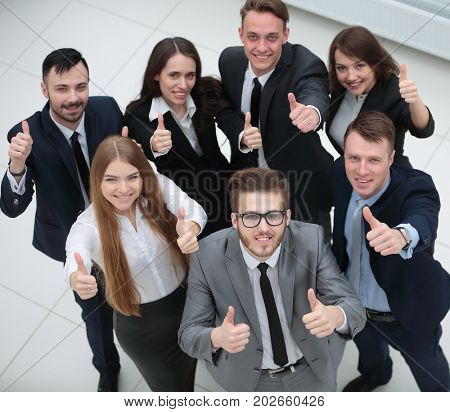 triumphant business team raised a thumbs up