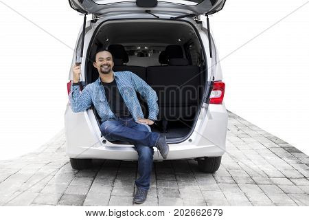 Photo of young afro man smiling at the camera while holding a key new car and sitting on the back of his car