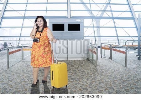Overweight young woman speaking on a mobile phone while standing with a baggage in the airport terminal