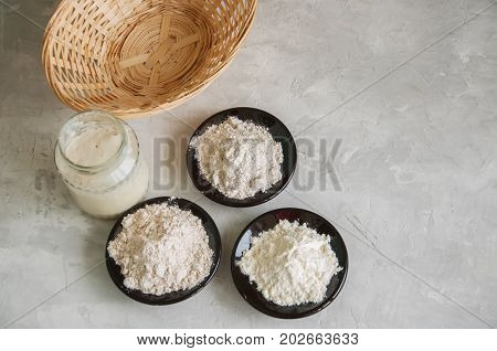 Sourdough In A Jar, Mix Of Flours, Basket For Proof On A Gray Stone Background. Baking Concept.