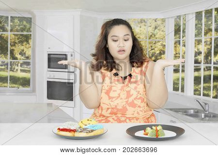 Fat woman looks confused to choose a vegetable salad or donuts while sitting in the kitchen