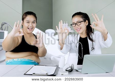 Picture of an Asian female doctor and overweight patient showing OK sign in the clinic