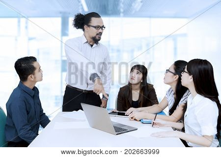 Afro male manager pointing at a laptop computer while scolding his employees in the meeting room