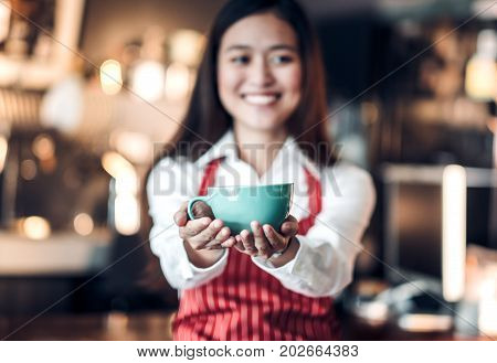 Close up on coffee up with blur asian woman barista holding mug with two hand with smiling face at cafe bar backgroundFocus on coffee up.