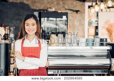 Asian female barista wear red apron crossed her arms at counter bar in front of coffee making machine with smile facecafe service conceptowner business start up.