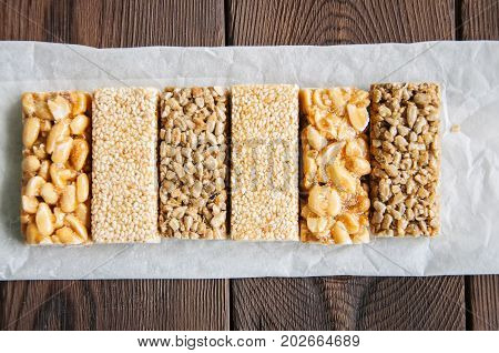Snacks - mix of energy bars with peanut sesame and sunflower seeds on a wooden background