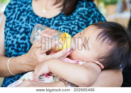 Closeup of baby feeding milk from baby's bottle. Family concepts