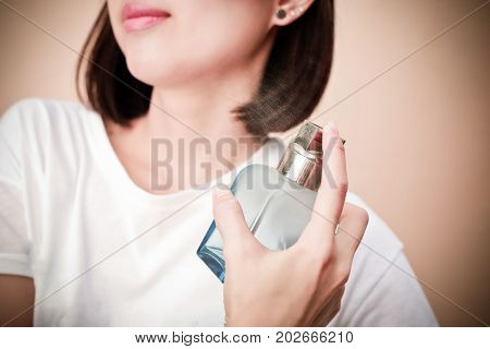 Young beautiful woman holding bottle of perfume and smelling aroma.