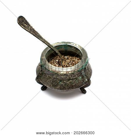Old vintage brass food bowl with spoon isolated.