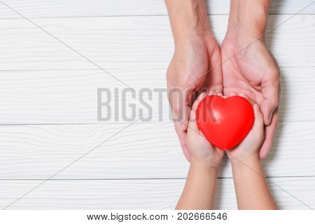 Father Day's and Mother's Day. Man holds his hands son supporting red heart.