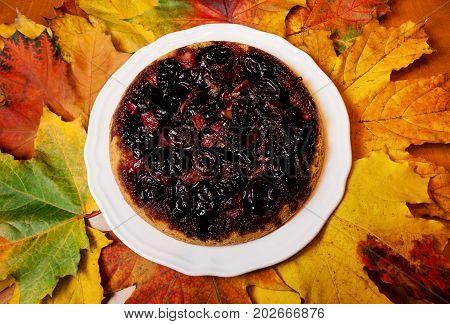 Homemade plum cake and autumn maple leaves