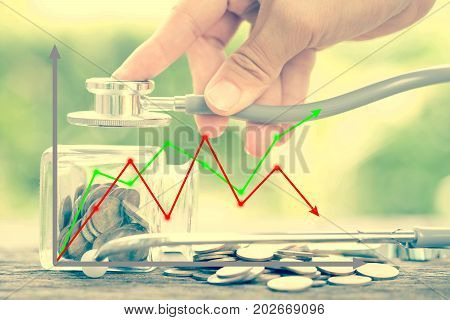 Graph and Stethoscope on bottle and coin on wooden background. Concept for finance health check or cost of business financial analysis audit or accounting.