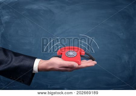 A businessman's palm hold a small red retro dial phone with lines showing soundwave emissions. Important call. Free number. Emergency connection.