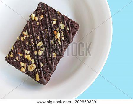 Chocolate brownies on a white plate, top view. blue background