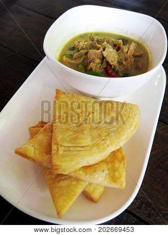 Thai , food, green curry chicken with coconut milk and fried Roti on a white plate with wooden background, side view