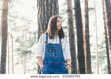 Beautiful young woman in jeans overalls standing in woodland in the evening