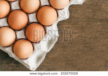 Fresh eggs in egg rack put on wood table. Prepare chicken eggs for cooking or bakery on rustic wood table. Top view or flat lay concept of fresh eggs with copy space for background or wallpaper. Eggs in egg rack in top view with copy space.