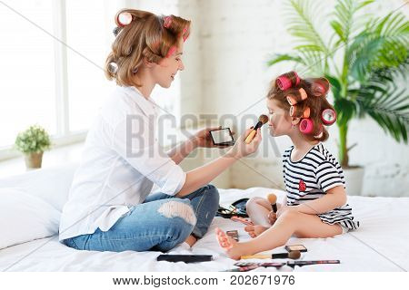 happy family Mother and baby daughter in curlers doing makeup on bed