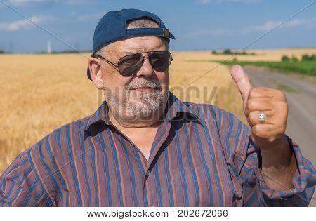 Outdoor portrait of a bearded senior man standing on a roadside beside agricultural field with ripe wheat