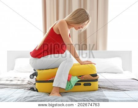 Young woman trying to pack her luggage at home. Luggage overweight concept