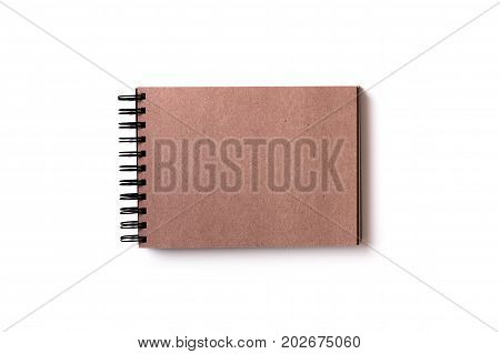 Horizontal aligned isolated sketchbook mock up with blank brown craft paper on white background. Top view flat lay.
