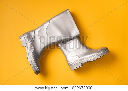 Autumn creative background: stylish silver marching rain boots composed interestingly on orange background. Top view. Flat lay.
