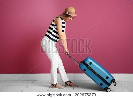 Young woman with suitcase near color wall. Luggage overweight concept