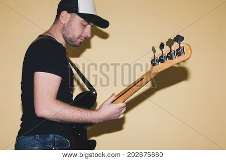Grown up hipster playing bass guitar. Background with free space, electric objects. Hobby for men, music concept