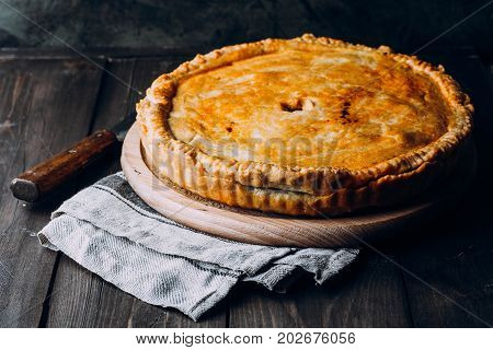 Fresh Whole Meat pie on the wooden board on table background. Pie with cabbage and minced beef
