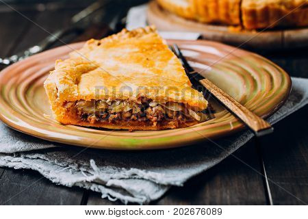 A piece of Fresh Meat pie on the wooden board on table background. Pie with cabbage and minced beef