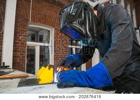 А man welder in a black work jumpsuit in a black welding mask and blue protective mitts brews an metal arc welding machine in the street on a summer day in the background a bumpy old wall