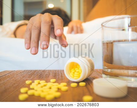 Sick woman covered with a blanket lying in bed with high fever and a flu focus on a hand. Healthcare medical supplements concept.